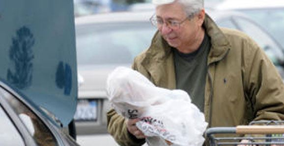 Man Moving Plastic Bag From Cart to His Vehicle